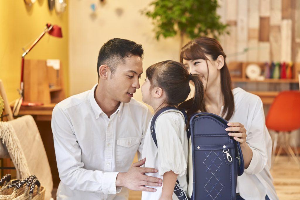 ランドセルを背負う女児と父母